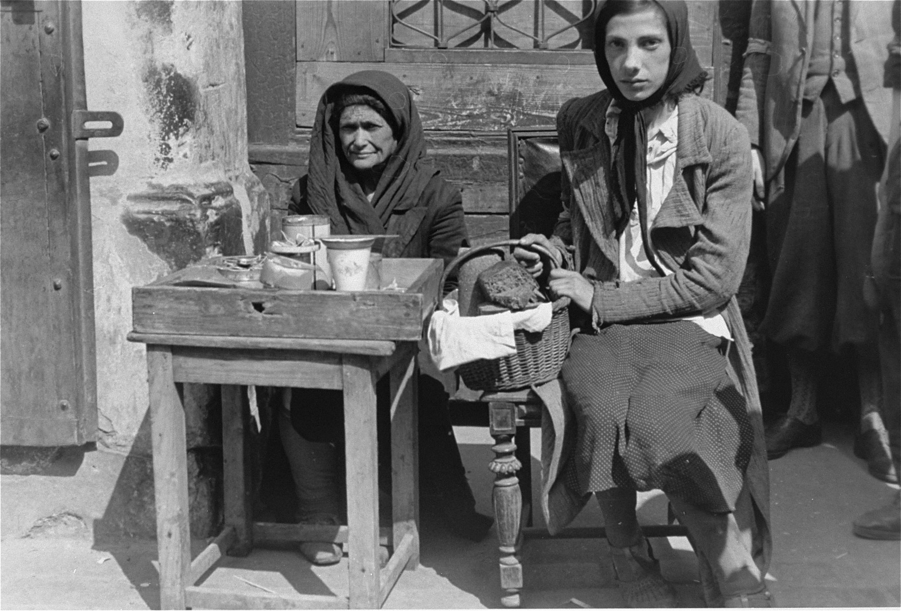 Two women sell bread and hot tea on the street in the Warsaw ghetto.
