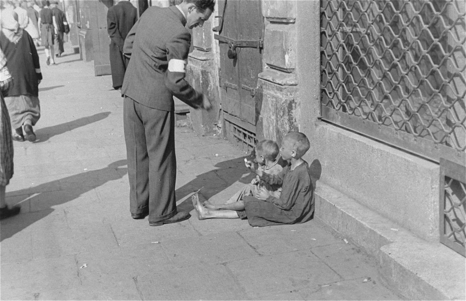 A man stops to help two destitute children on the street in the Warsaw ghetto.