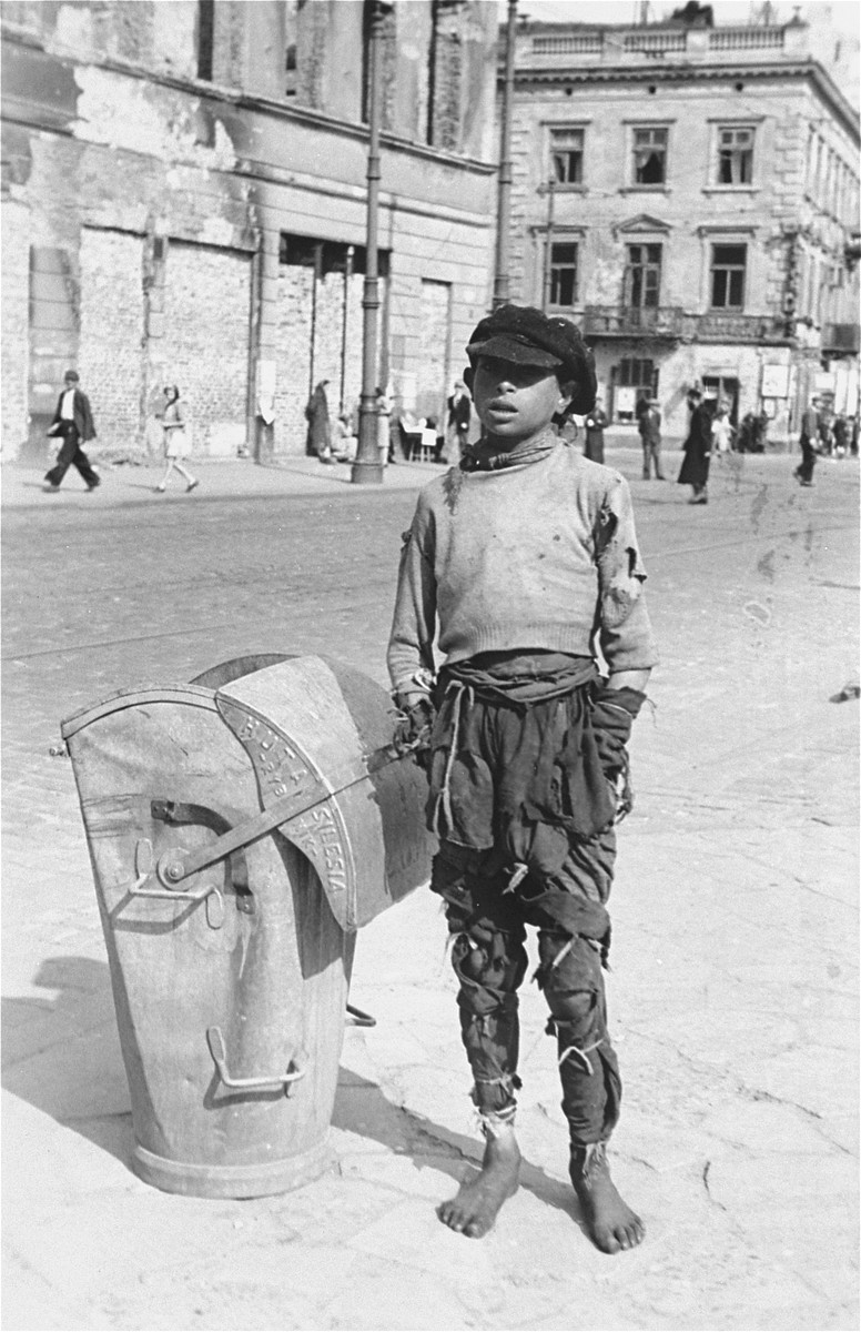 A destitute youth poses barefoot on the street in the Warsaw ghetto next to a trash can.