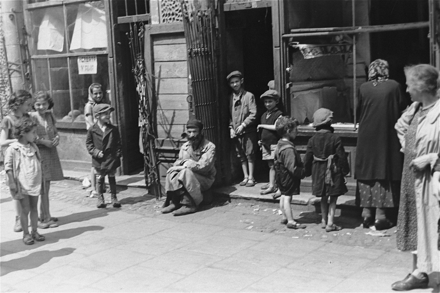 A group of Jews stands outside a shop whose windows were broken during the German invasion.  Due to a lack of materials, broken windows and doors could not be replaced.  While goods were still available, some proprietors built iron fences to protect their shops.