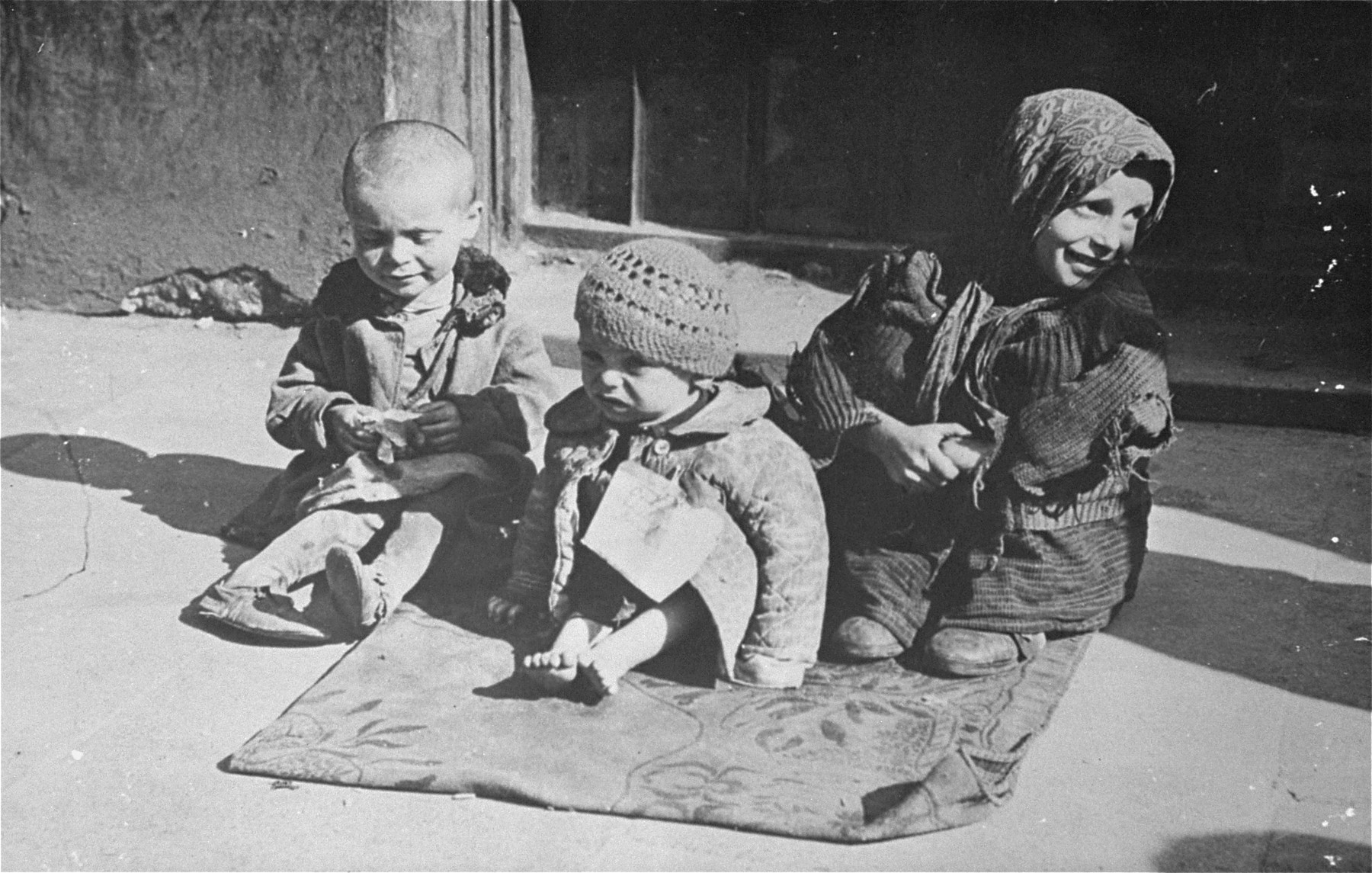 Three destitute young children sit on the pavement in the Warsaw ghetto.