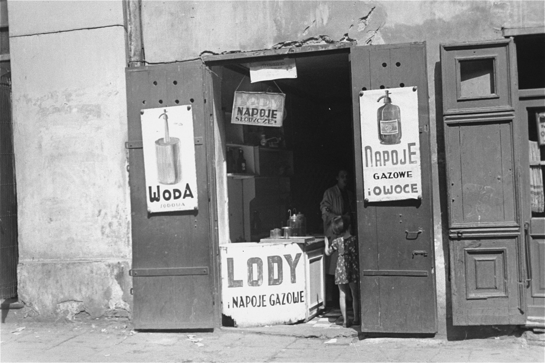 Signs posted at the entrance to a shop in the Warsaw ghetto advertise soft drinks and ice cream.