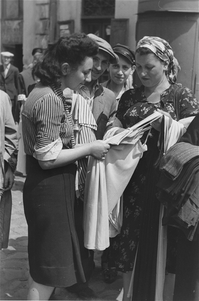 A young woman examines an item of clothing at an open air market in the Warsaw ghetto.