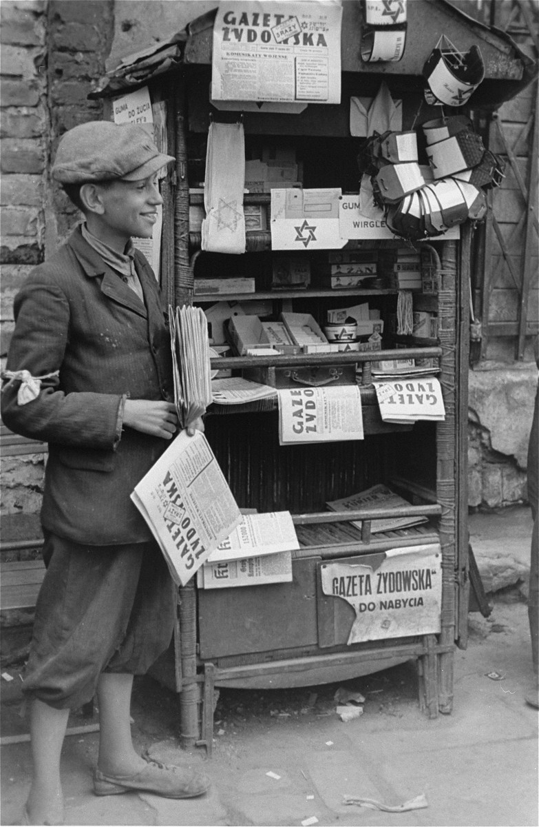 A teenage vendor sells newspapers and armbands in the Warsaw ghetto possibly on Muranowski Square.
