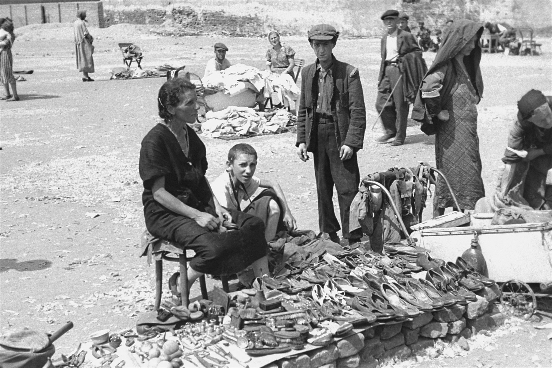 Vendors sell old shoes and other items of used clothing at an open air market in the Warsaw ghetto.