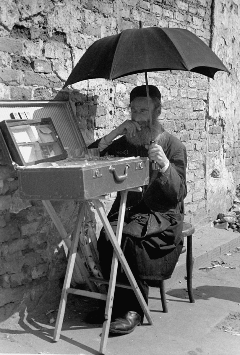 A Jewish vendor sitting on the street in the Warsaw ghetto shades himself with a large umbrella.