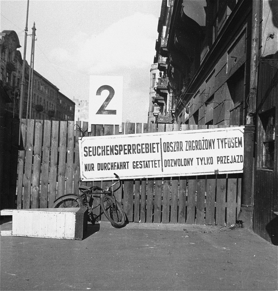 "A sign in German and Polish posted at entrance 2 to the Warsaw ghetto reads, ""Area closed because of epidemic. Only through traffic permitted.""    Joest's original caption reads: ""I passed through this gate into the ghetto, which was forbidden for soldiers without the proper permission.  The signs warned of typhus.  Just  behind the gate stood vendors, even children, who tried to sell trinkets."""