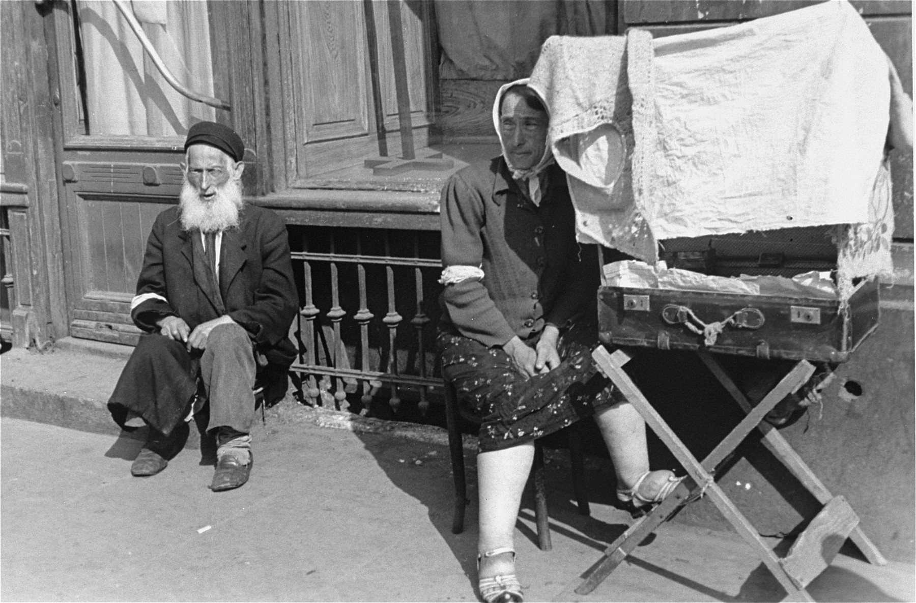 A female vendor sits on a street in the Warsaw ghetto next to an open suitcase containing her wares that has been covered with a dress to provide some shade.  An elderly, bearded man sits nearby.