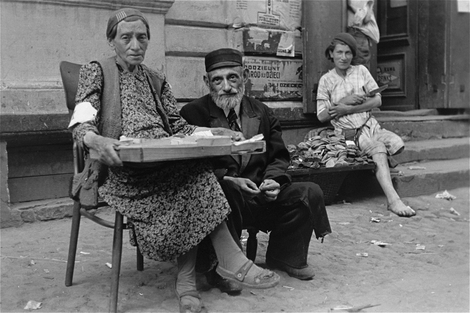 An elderly couple sells goods on the street in the Warsaw ghetto.