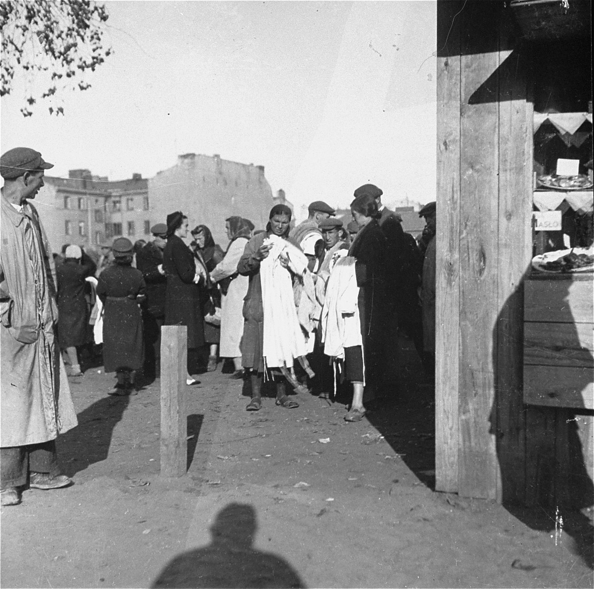 """Inhabitants of the Warsaw ghetto sell clothing to Polish customers at an open air market.    Joest's original caption reads: """"Those with the white armbands, the Jews, were the ones selling.  Those without armbands, the Poles, were the buyers."""""""