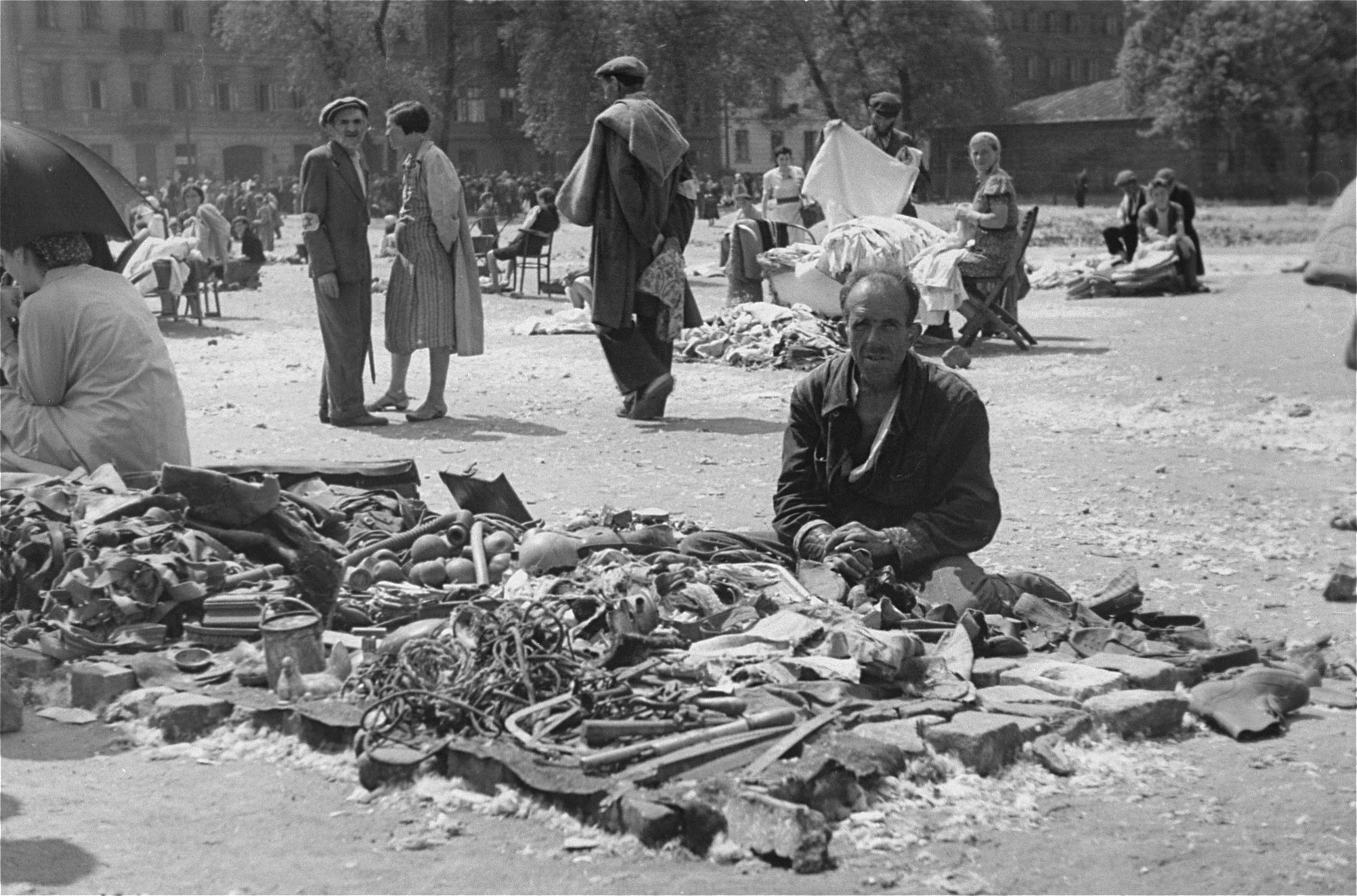 A Jewish vendor offers odds and ends for sale at an open air market in the Warsaw ghetto.