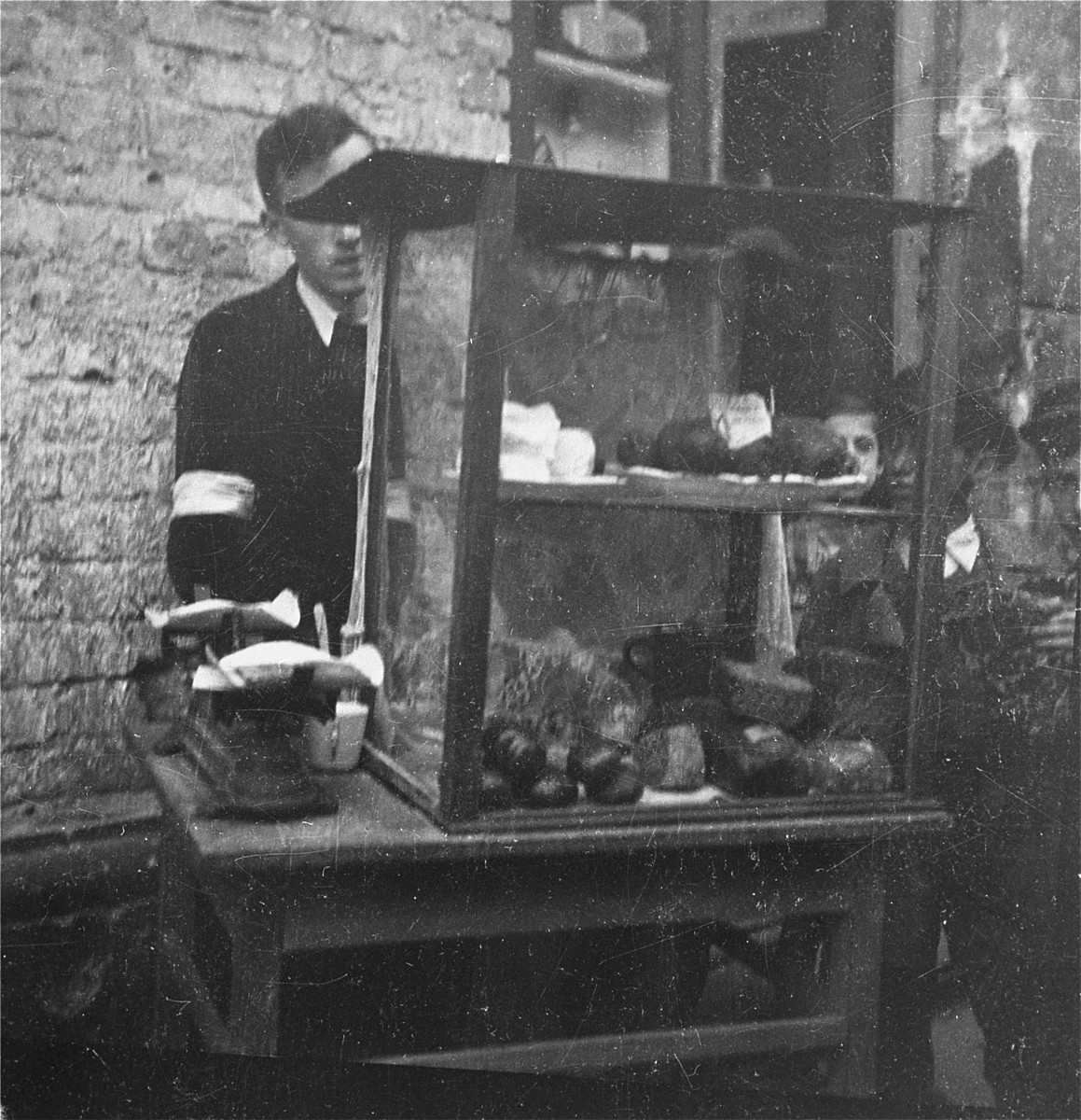"""A vendor on the street in the Warsaw ghetto offers bread and cheese for sale.   Joest's original caption reads: """"This man sold bread and cheese on the street.  Children surrounded his glass case, but could not buy anything."""""""