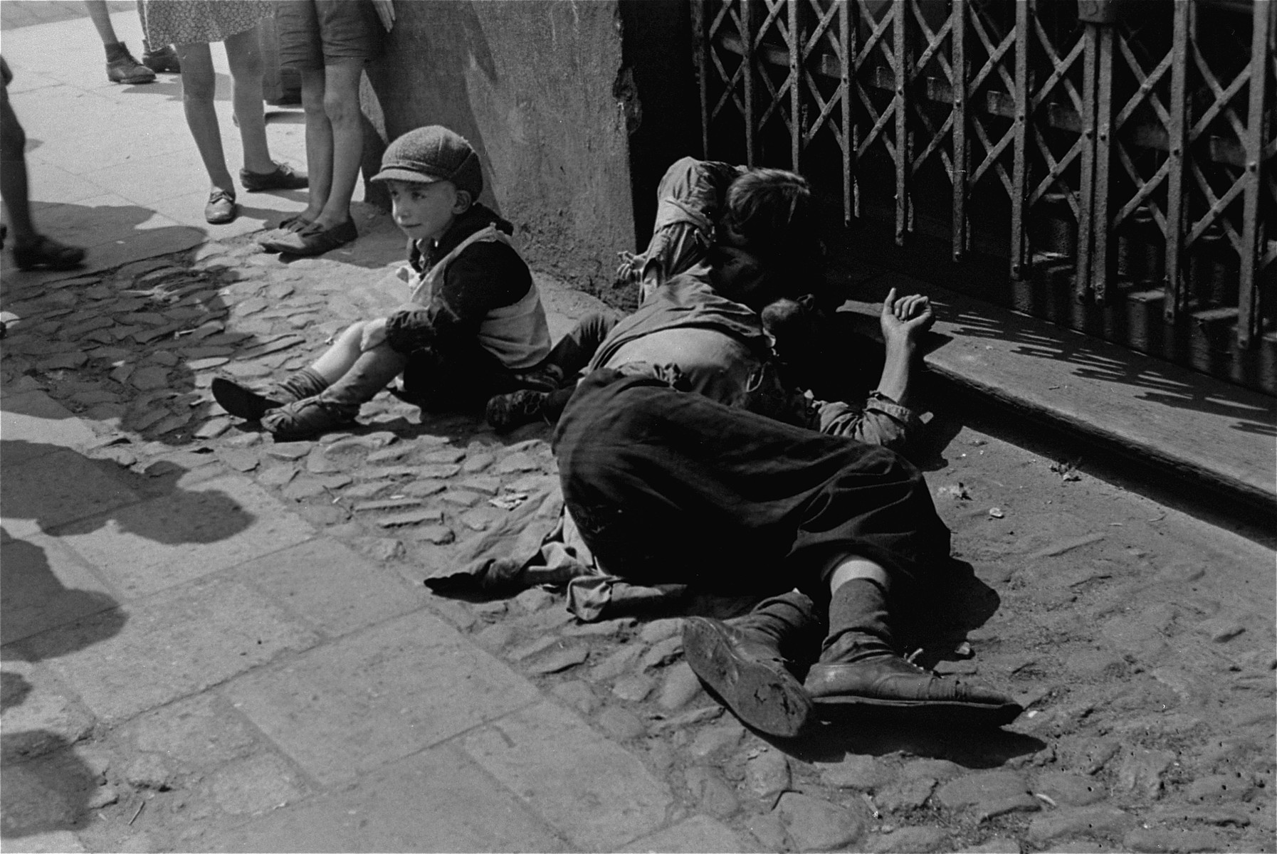 A destitute father and his two children sit on the street in the Warsaw ghetto.