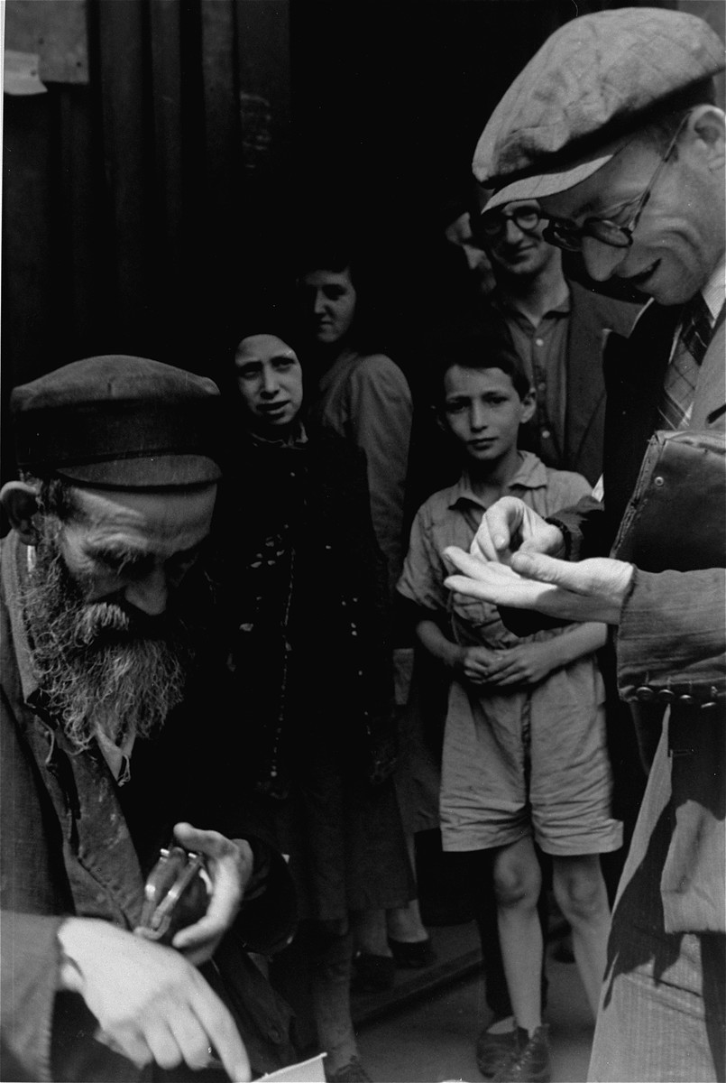 Two men conduct a business transaction on the street in the Warsaw ghetto.