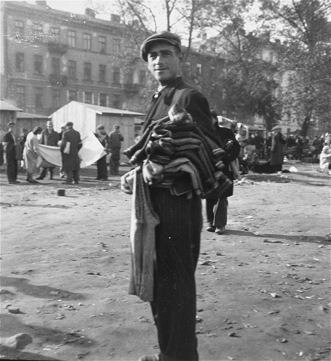 "A man offers sweaters for sale at an open air market in the Warsaw ghetto.    Joest's original caption reads: ""This man had an entire armful of new sweaters.  He wanted me to purchase one."""