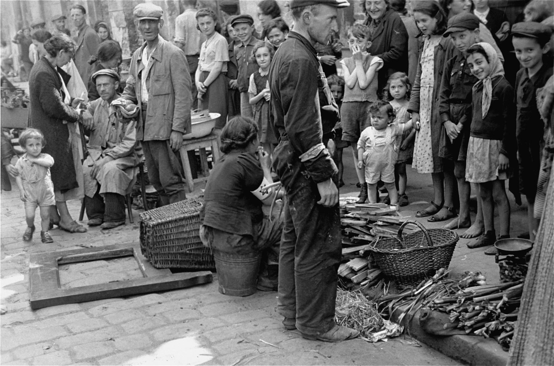 Jews gather around a couple selling kindling on the street in the Warsaw ghetto.
