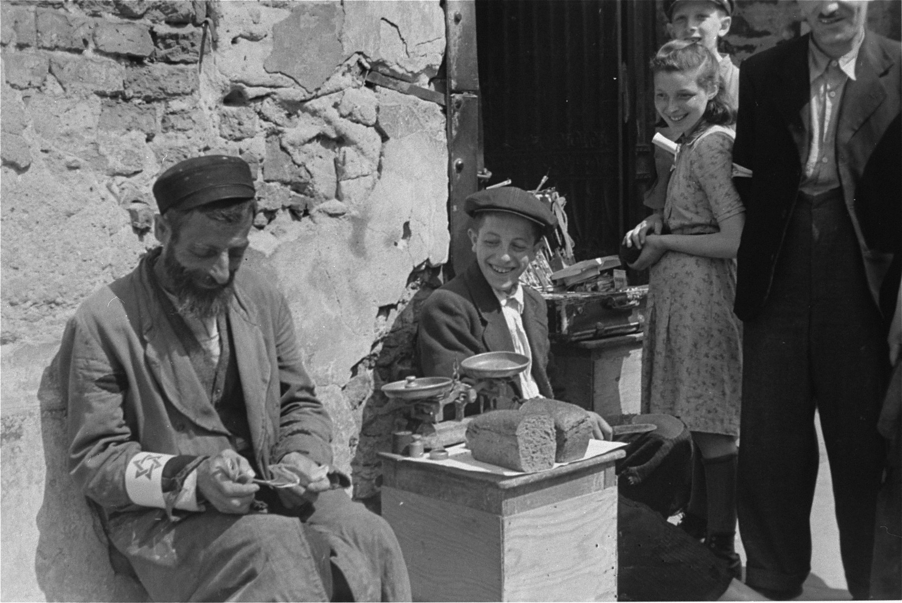 A Jewish man and youth sell bread on the street in the Warsaw ghetto.