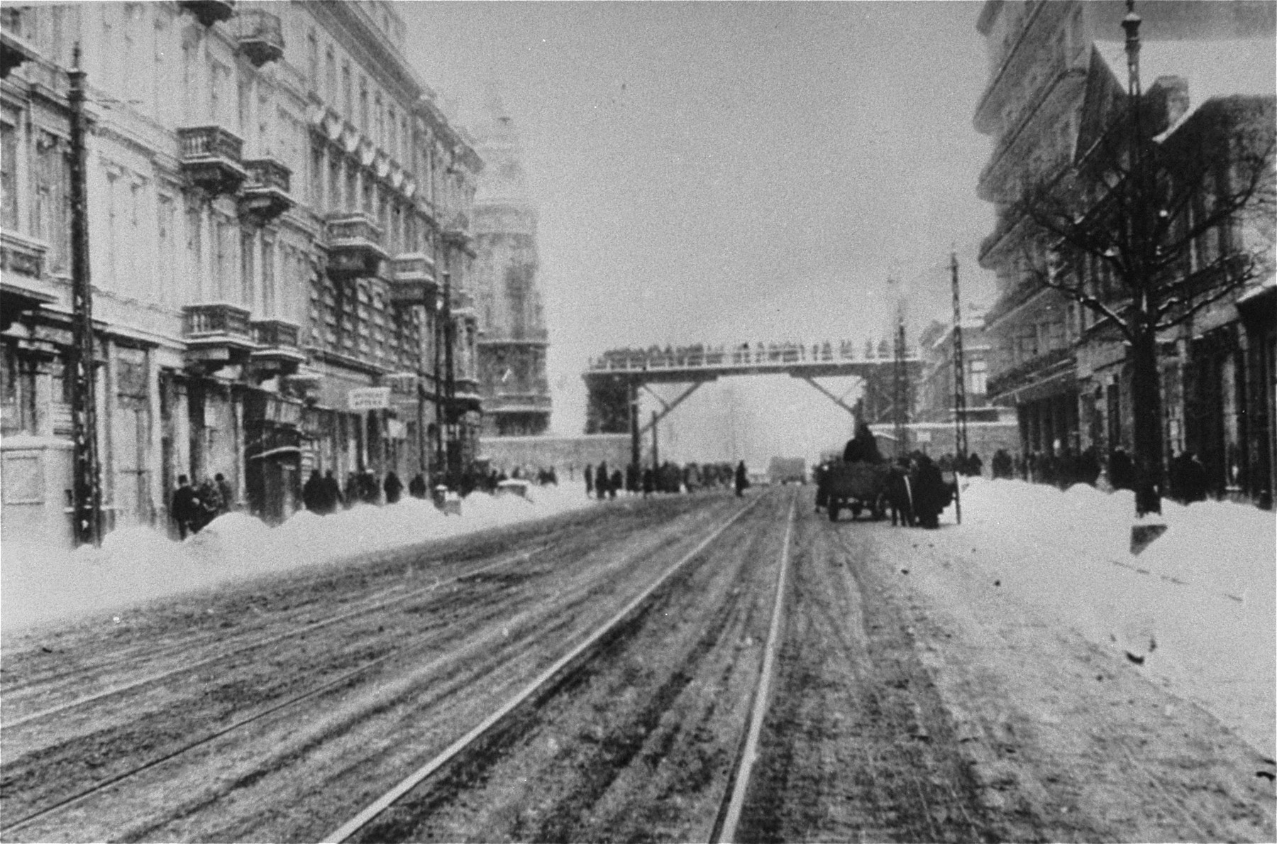View of a street that divided the Warsaw ghetto.  A bridge that connected the two parts of the ghetto is visible.