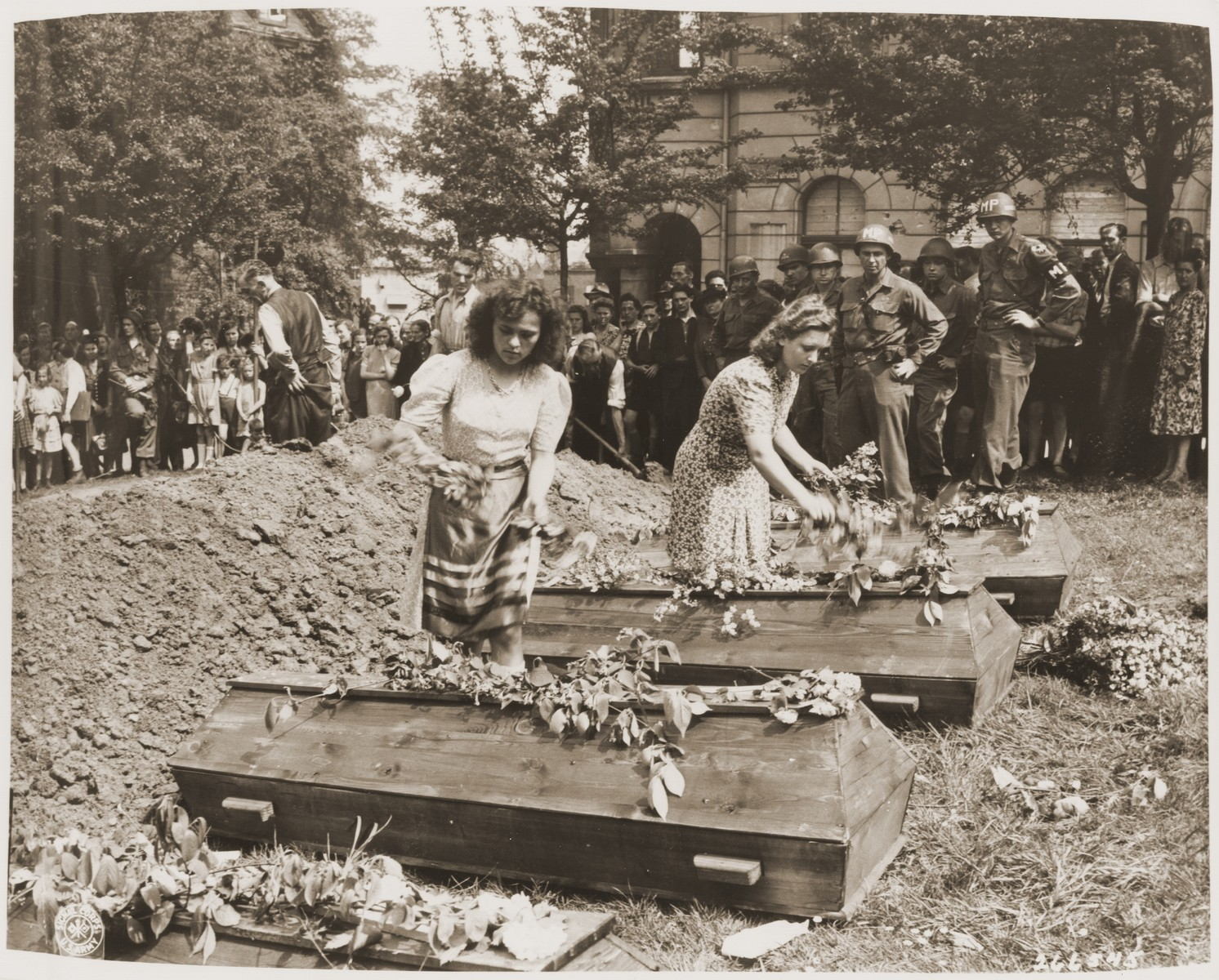 German girls place flowers on the coffins of seven Russian victims hung by their captors in Muehlheim.   The bodies were recovered by German civilians under the supervision of U.S. troops of the 194th Gilder Regiment, 17th Airborne Division.  The townspeople of Muehlheim were forced to attend funeral services for the victims.