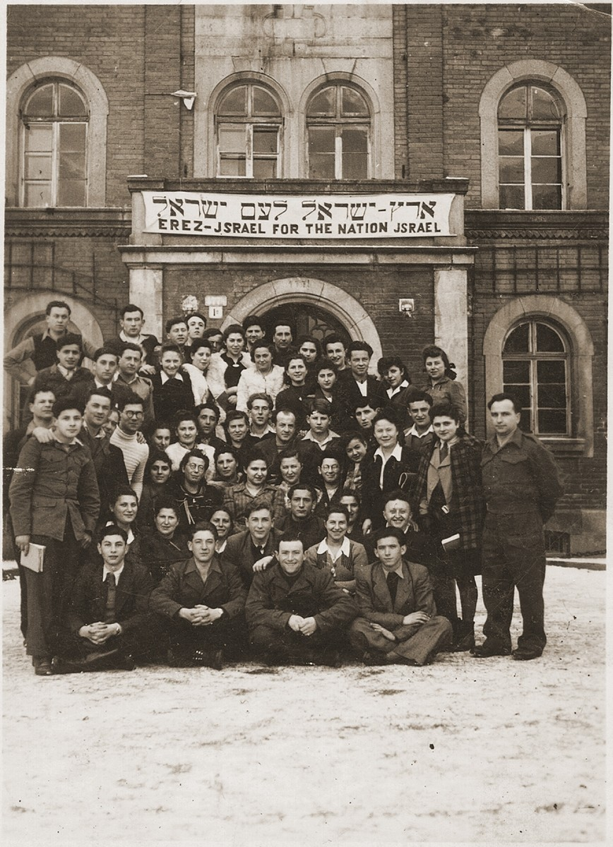 "Group portrait of Jewish DPs in Deggendorf, Germany, who pose beneath a Zionist banner which reads ""Eretz Israel [the Land of Israel] for the Nation Israel"", in Hebrew and English."