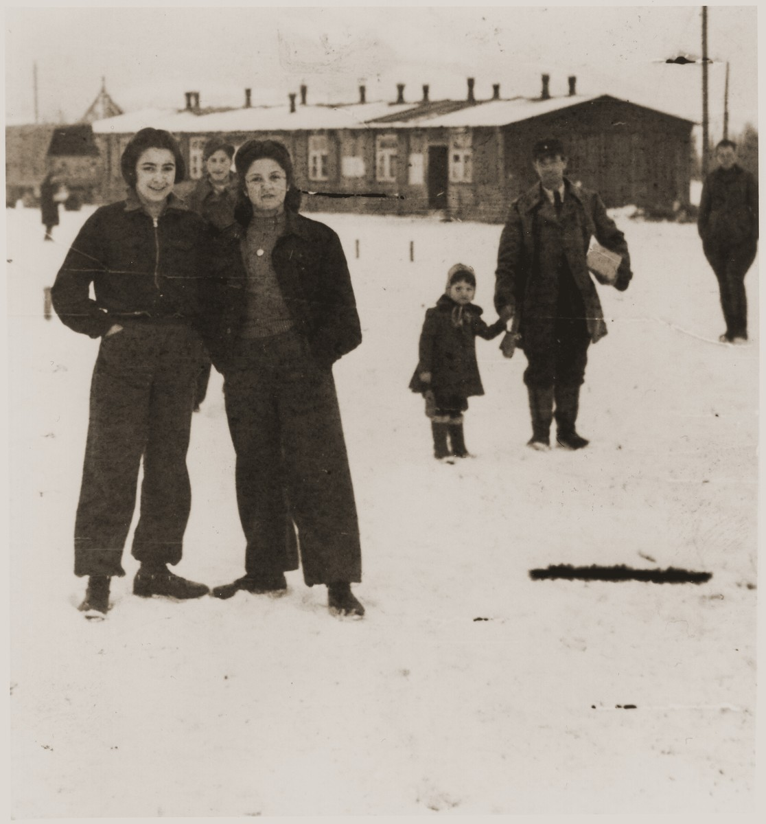 Helen Verblunsky stands with a friend in the snow outside the barracks of an unidentified DP camp in the British zone.
