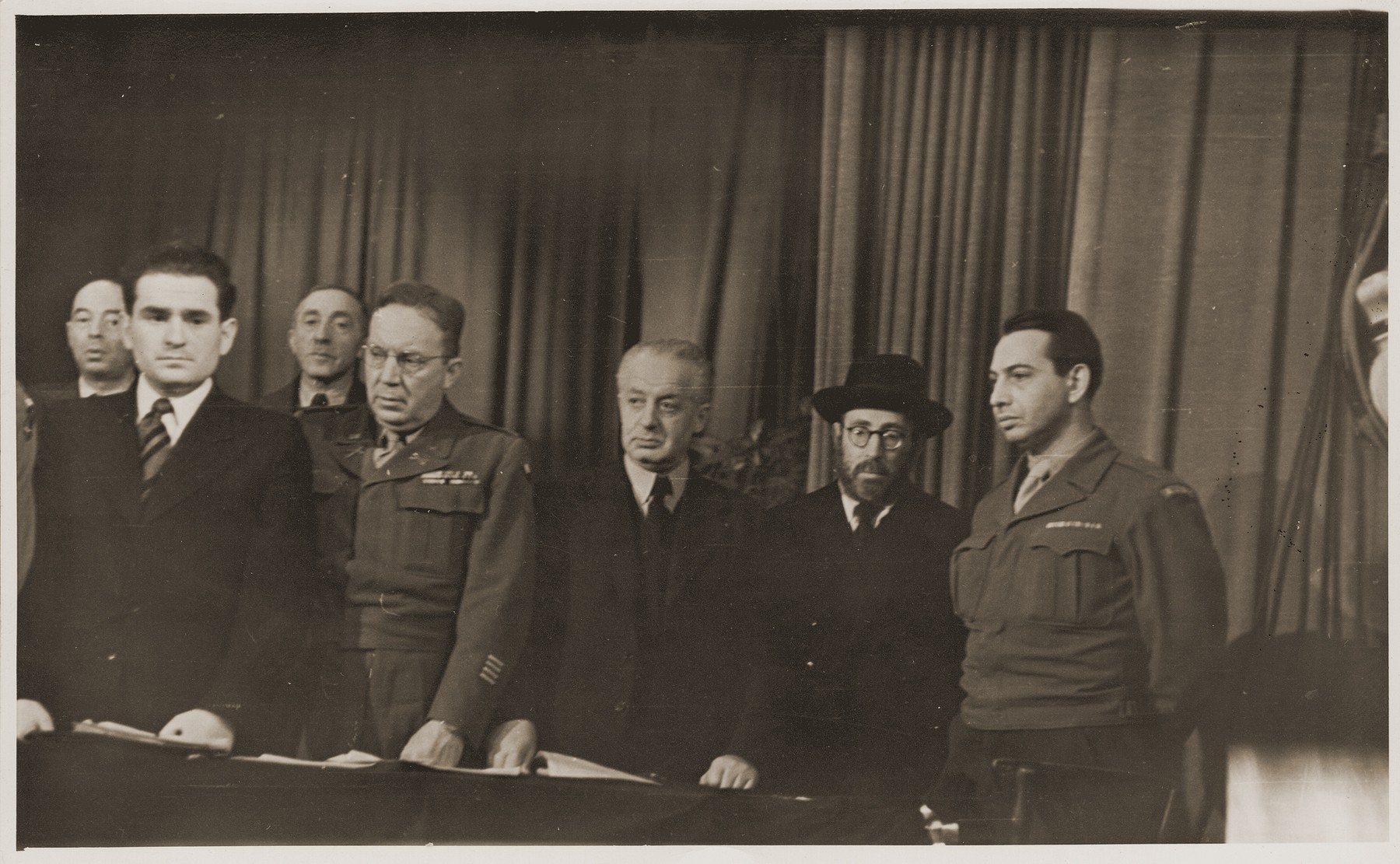 Group portrait of DP leaders on the dias at a conference sponsored by the Central Committee of the Liberated Jews in the U.S. Zone of Germany.   Among those pictured are Leo Schwarz (far right); Rabbi Samuel Snieg (next to Schwarz); and Leon Retter (front, left).