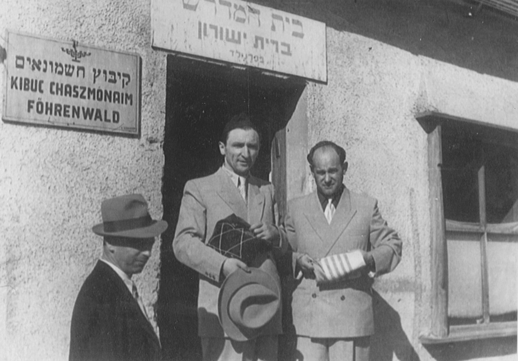 Meyer Lifschitz and a friend, Cantor Jonas Garfinkel,  leave the synagogue in the Foehrenwald DP camp.    Cantor Garfinkel is standing in the center holding the tallis bag.
