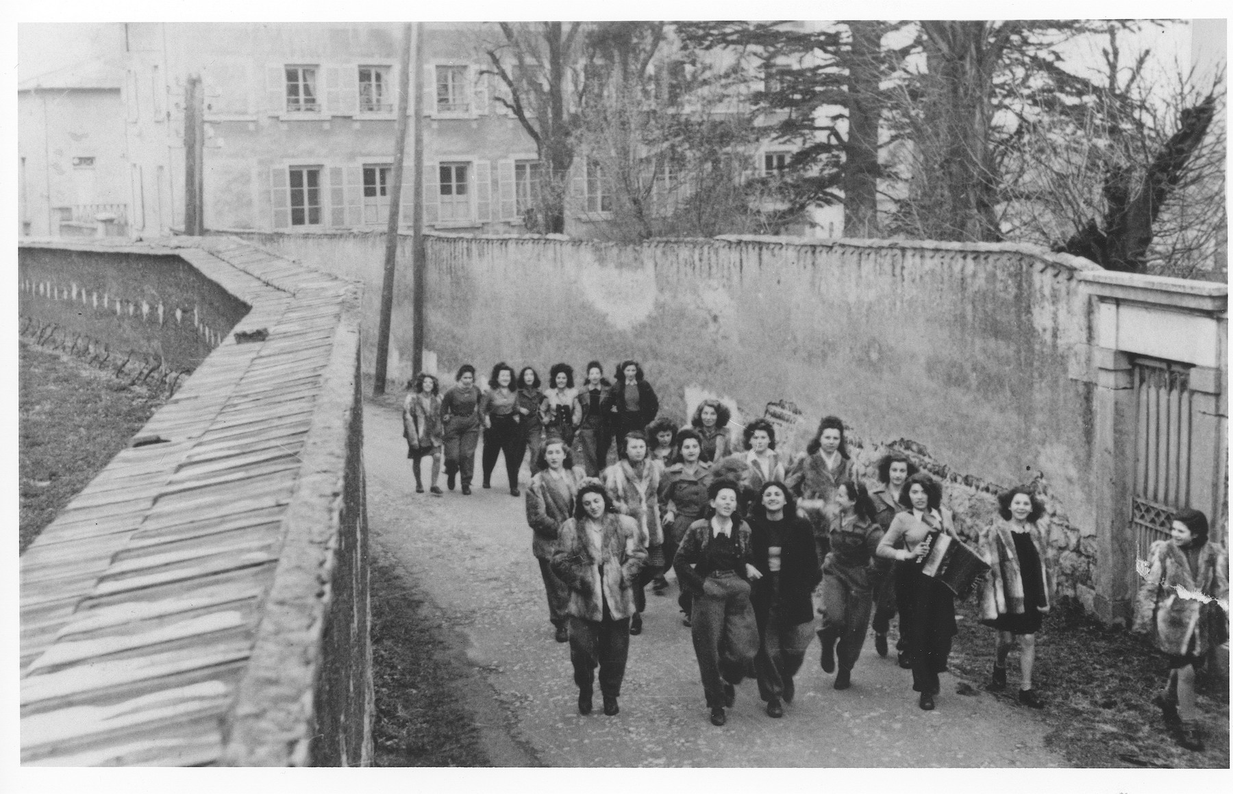 Teenage girls from the OSE children's home, Le Tremplin, walk along a narrow street wearing rabbit jackets sent to them from abroad.