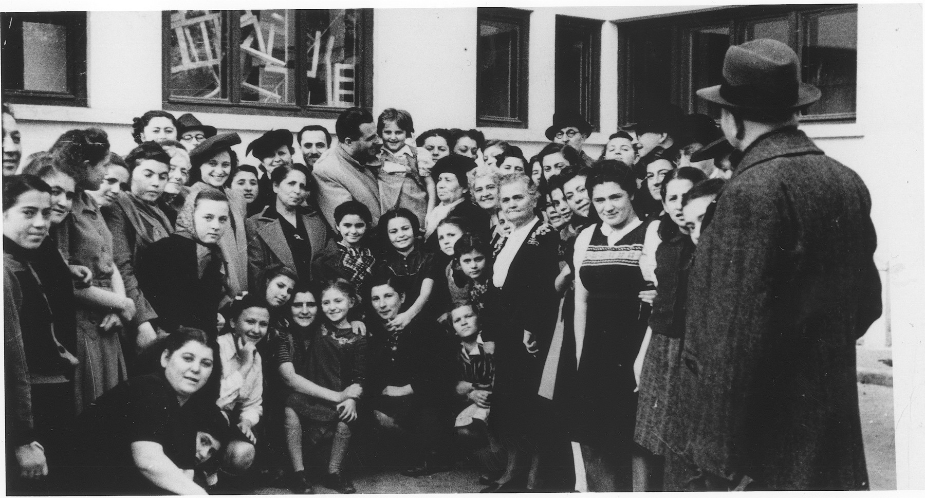 Social welfare workers involved in the effort to repatriate the Jewish orphans from Transnistria, pose with some of the returning children at an orphanage in Bucharest.   Among those pictured are Anny (Hubner) Andermann (back row in the feathered beret) and Betty Schwefelberg (seventh from the left with a large hat).