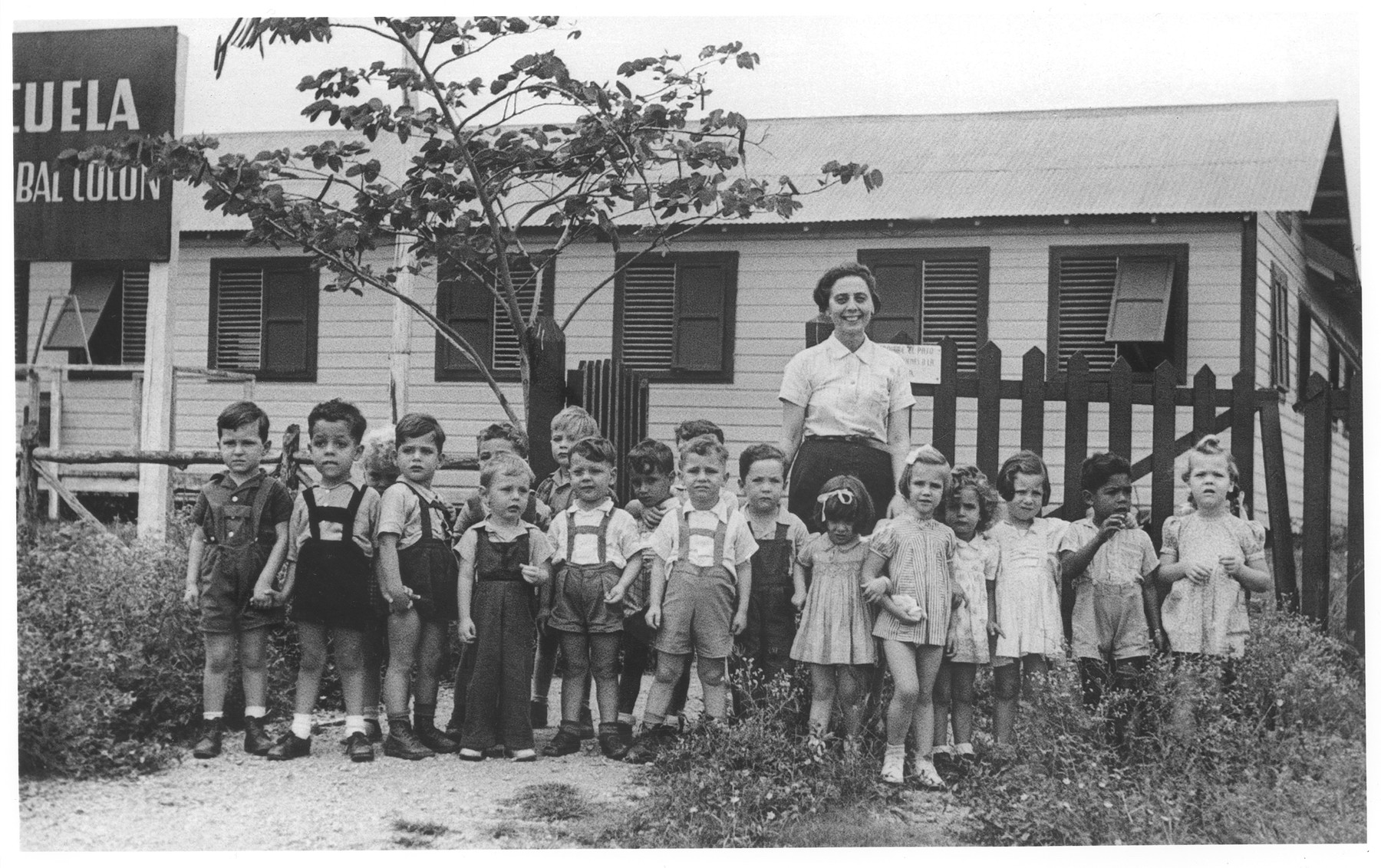 Group portrait of Jewish refugee preschoolers at the Christobal Colon school in Sosua.  Behind them stands their teacher, Hella Blum.  Among those pictured are Franklin Hess, Fritz Rosenzweig, Henry Spitzer, Rene Kirchheimer, Renee Hurwicz, Peter Papernik and Peter Dicker, Hank Goldman, Henry Spitzer, Edi Brinehalter.  The Christobal Colon school was founded in 1941 by DORSA the Dominican Republic Settlement Association, for the children of Jewish settlers.  The school consisted of two wooden buildings, one for the kindergarten and one for the elementary school.  The curriculum though similar to that of other Dominican schools, also included English and Jewish studies.