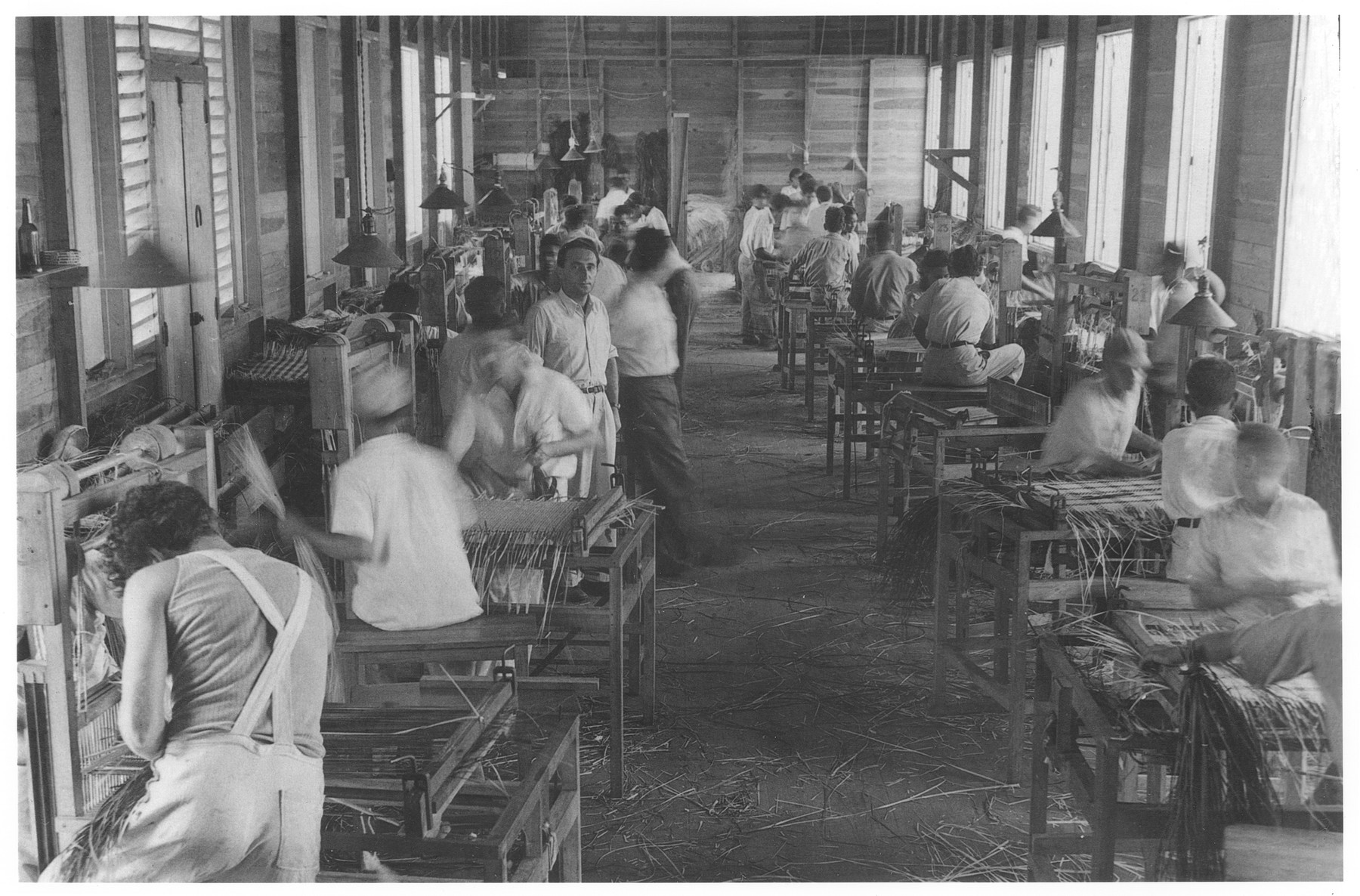 Jewish refugees work in a straw factory making handbags for export to America.