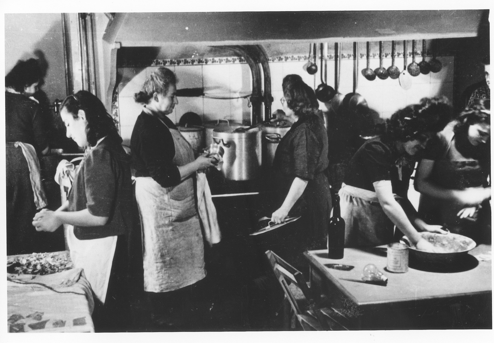 Women prepare food in the kitchen of the Saint Germain children's home.