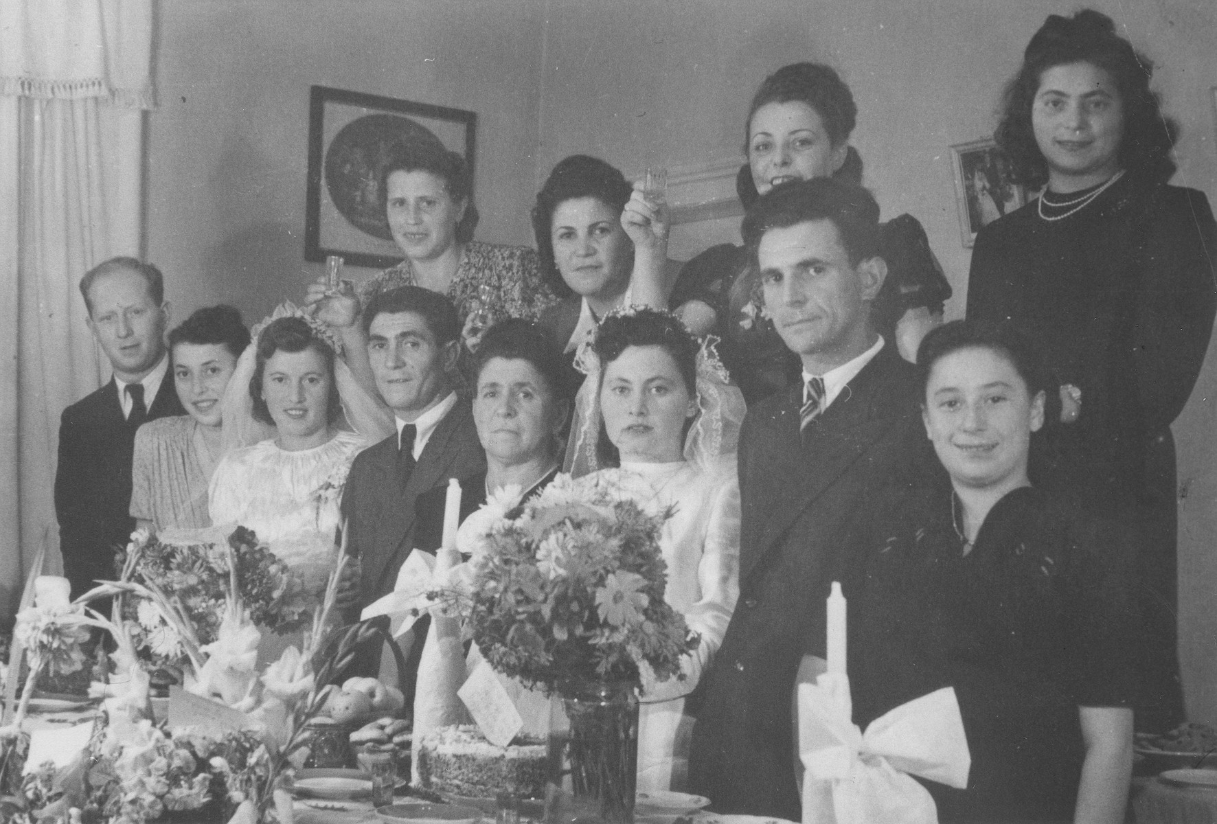 Family and friends celebrate the double wedding of Israel and Zlata (Distel) Malcmacher and Motel and Lola (Rolnik) Malcmacher.  Pictured from left to right are: (front row) Srulek and Natke (Rolnik) Katzman; Lola and Motel Malcmacher; Chaja Sara Malcmacher; Israel and Zlata Malcmacher; and Nechame (Probe) Rothschild; (back row): Chele (Huberman) Malcmacher; Rushke (Malcmacher) Borenstein; Sabina (Warshawsky) Rosenzweig; and Hadassah (Abramovich) Wandersman.