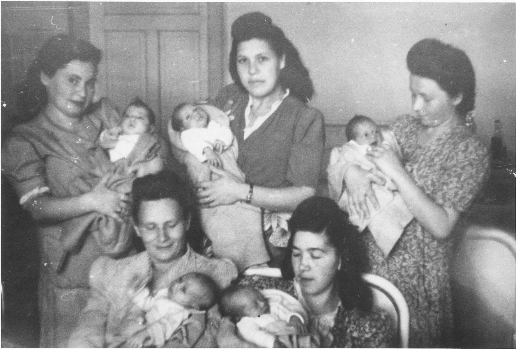 Five new mothers pose with their infants in the maternity ward of the Elizabeth Hospital in the Feldafing displaced persons camp.  Among those pictured is Zlata (Distel) Malcmacher holding Rascha Riwka (top left).
