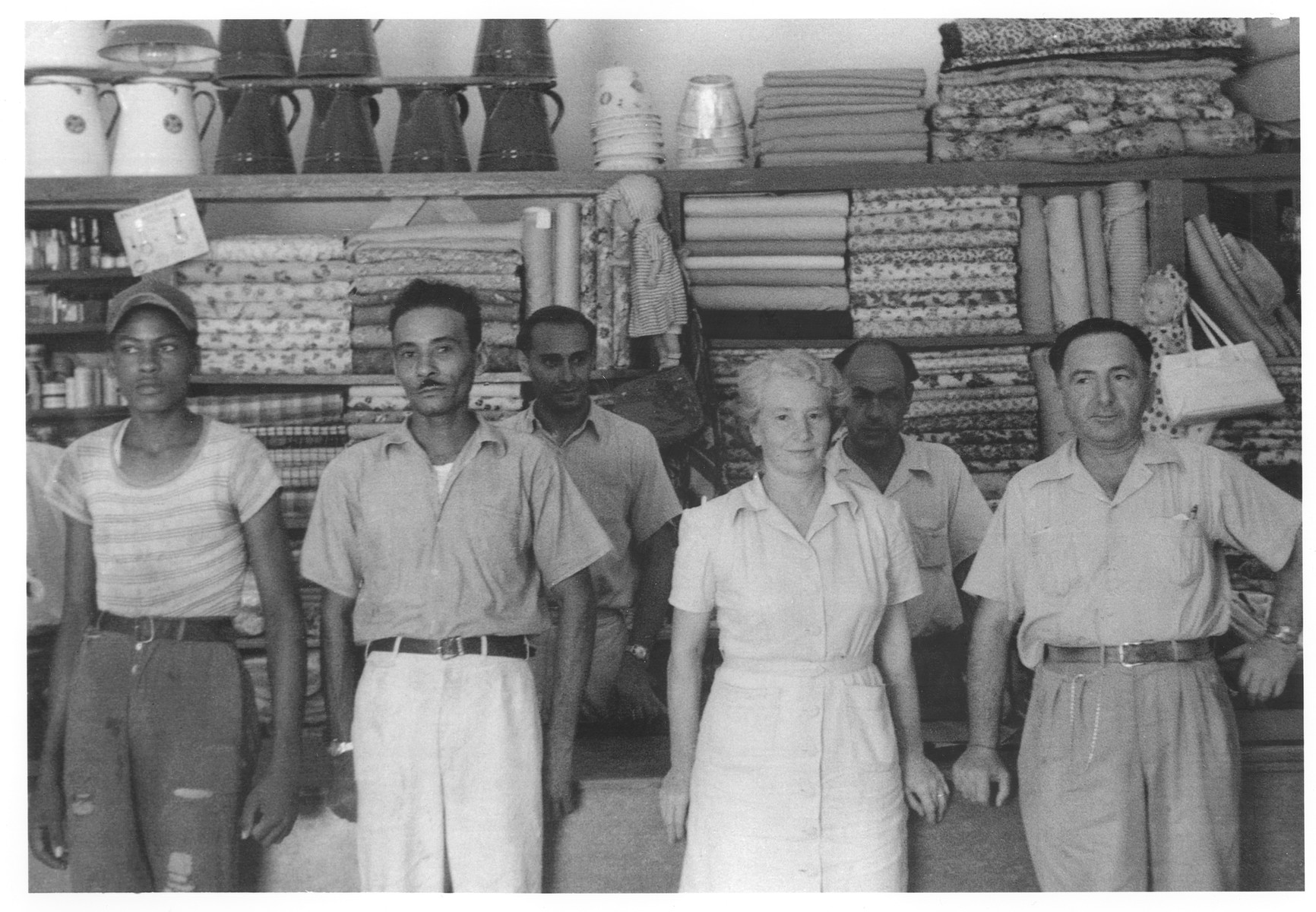 Group portrait of the staff of the El Colmado general store in Sosua.  In the first row (from left to right) are Jose Mena, Kaethe Kohn and either Mr. Strauss or Mr. Levy.  In the back row are Otto Kilbel and Pepi Mingelgruen.