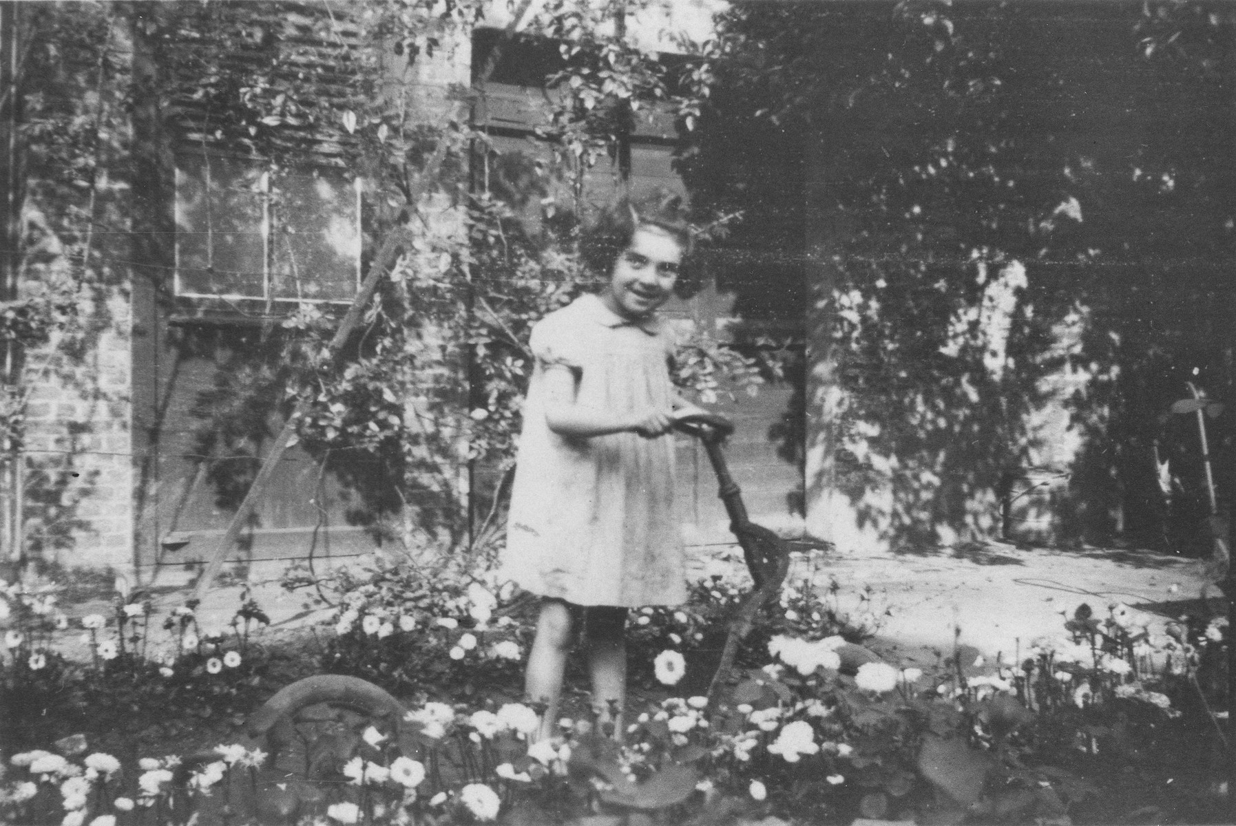 Rachelle Silberman, a Jewish child from Brussels who is living in hiding, poses in the garden of the Couvent des Soeurs Franciscaines [Convent of the Franciscan Sisters] in Brouges on her fifth birthday.