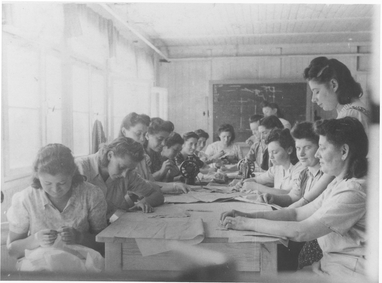 Women learn to sew in an ORT workshop in the Feldafing displaced persons camp.  Among those pictured are Zlata (Distel) Malcmacher (seated third from the right) and Chaya Zarenbrok (seated at the front left).
