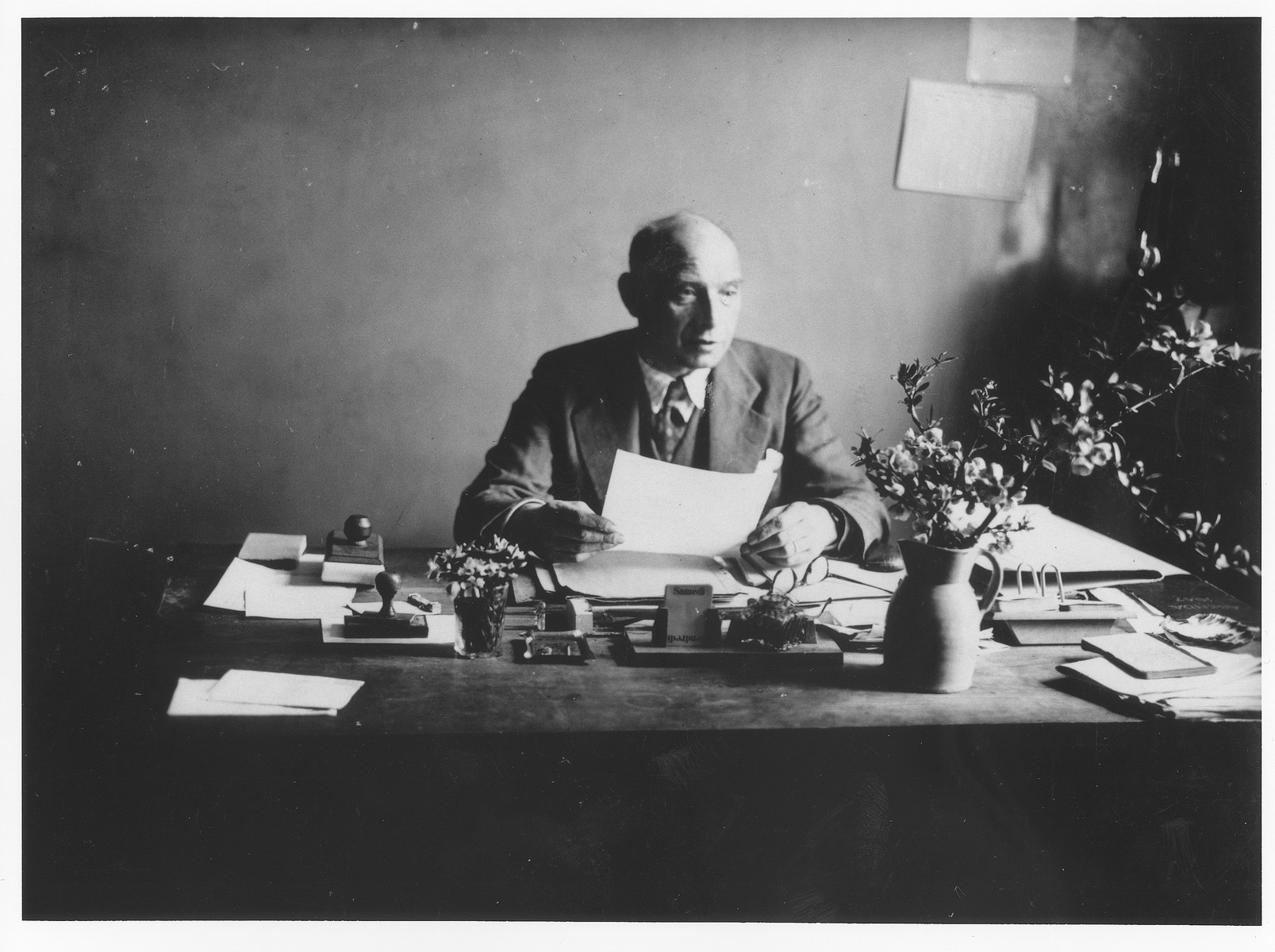 Mr. Dreyfus, the director of Saint Germain children's home, sits at his desk in his office.