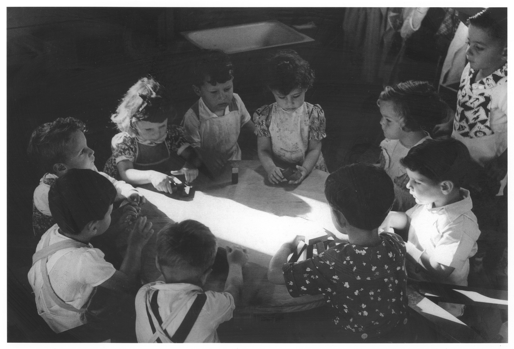 Young children play around a table in the Christobal Colon preschool.  The Christobal Colon school was founded in 1941 by DORSA the Dominican Republic Settlement Association, for the children of Jewish settlers.  The school consisted of two wooden buildings, one for the kindergarten and one for the elementary school.  The curriculum though similar to that of other Dominican schools, also included English and Jewish studies.