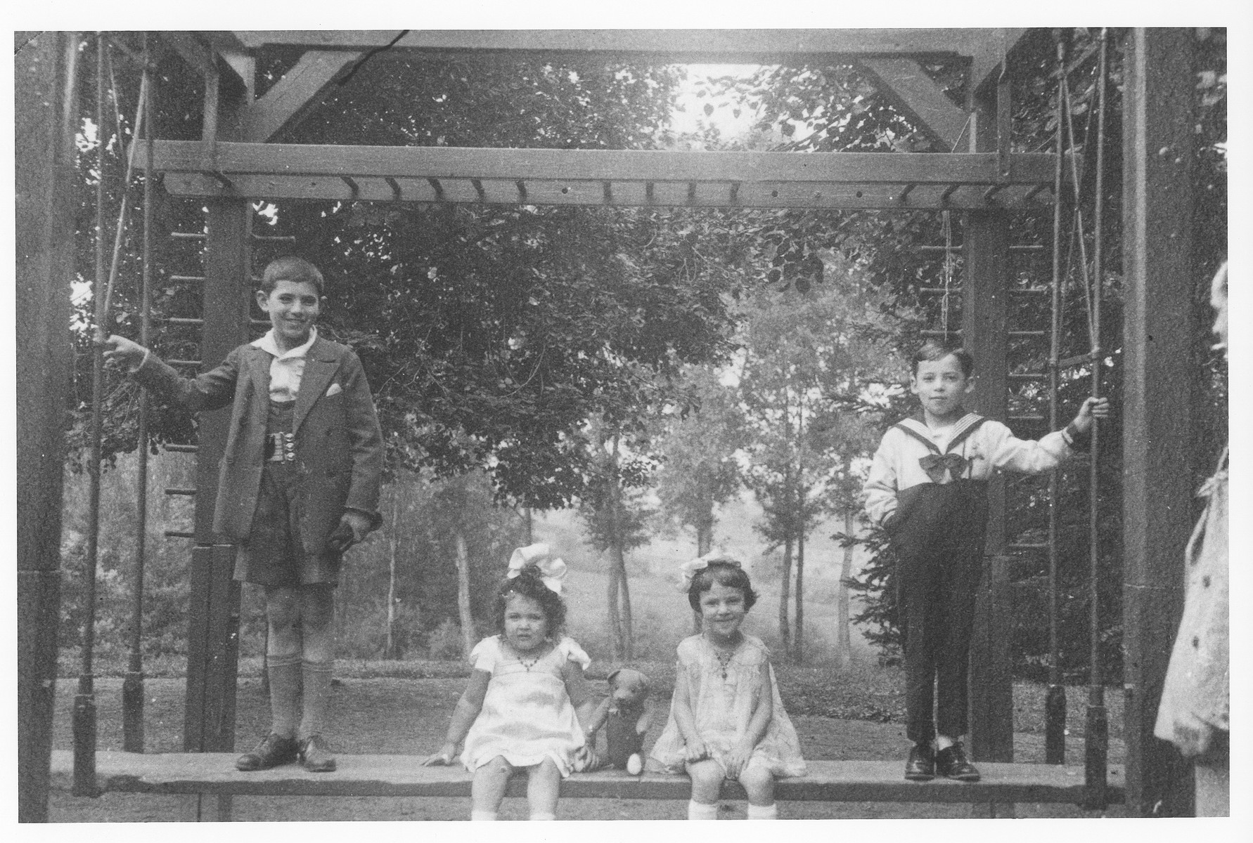 The Goldberg and Kamelgarn children pose on a swing set in a park in Luxembourg, where they were vacationing.  From left to right are Leon, Rose Goldberg, and Leah and Richard Kamelgarn.