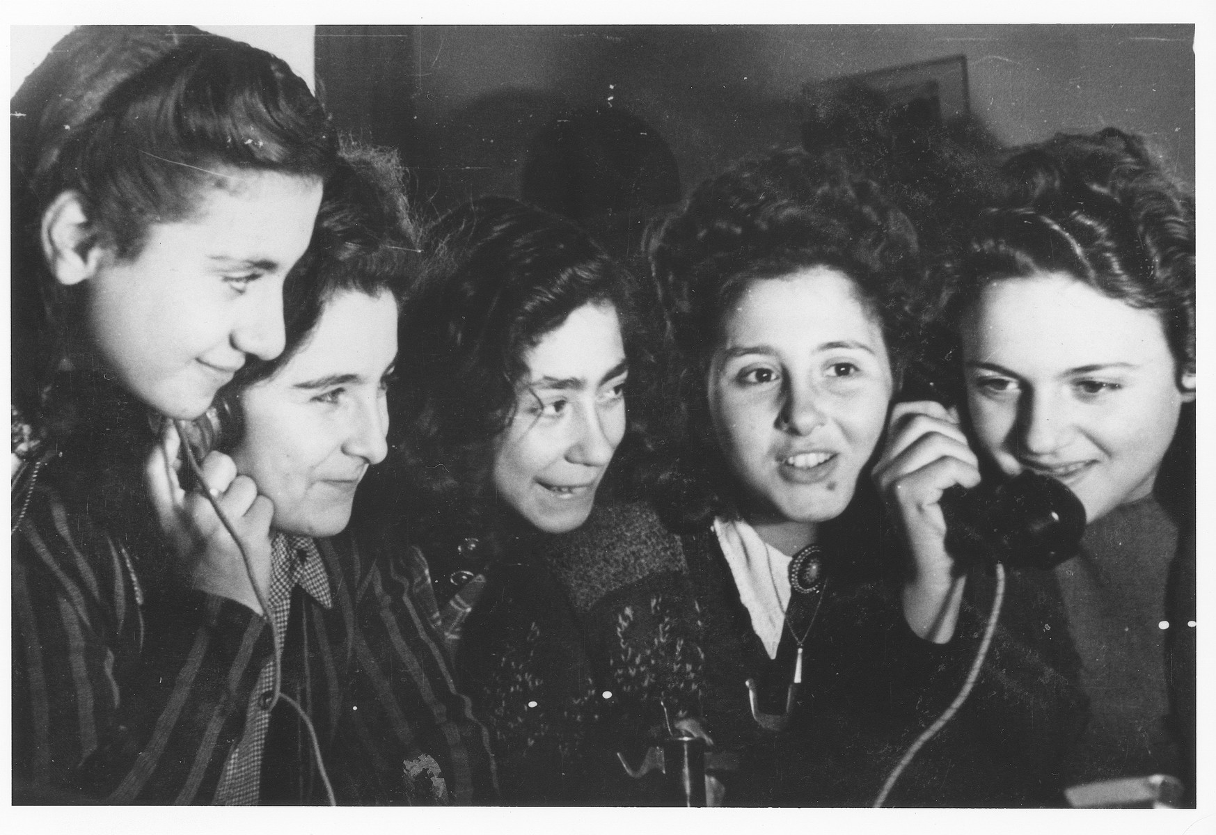 A group of teenage girls huddles around the telephones in the Le Tremplin OSE home.