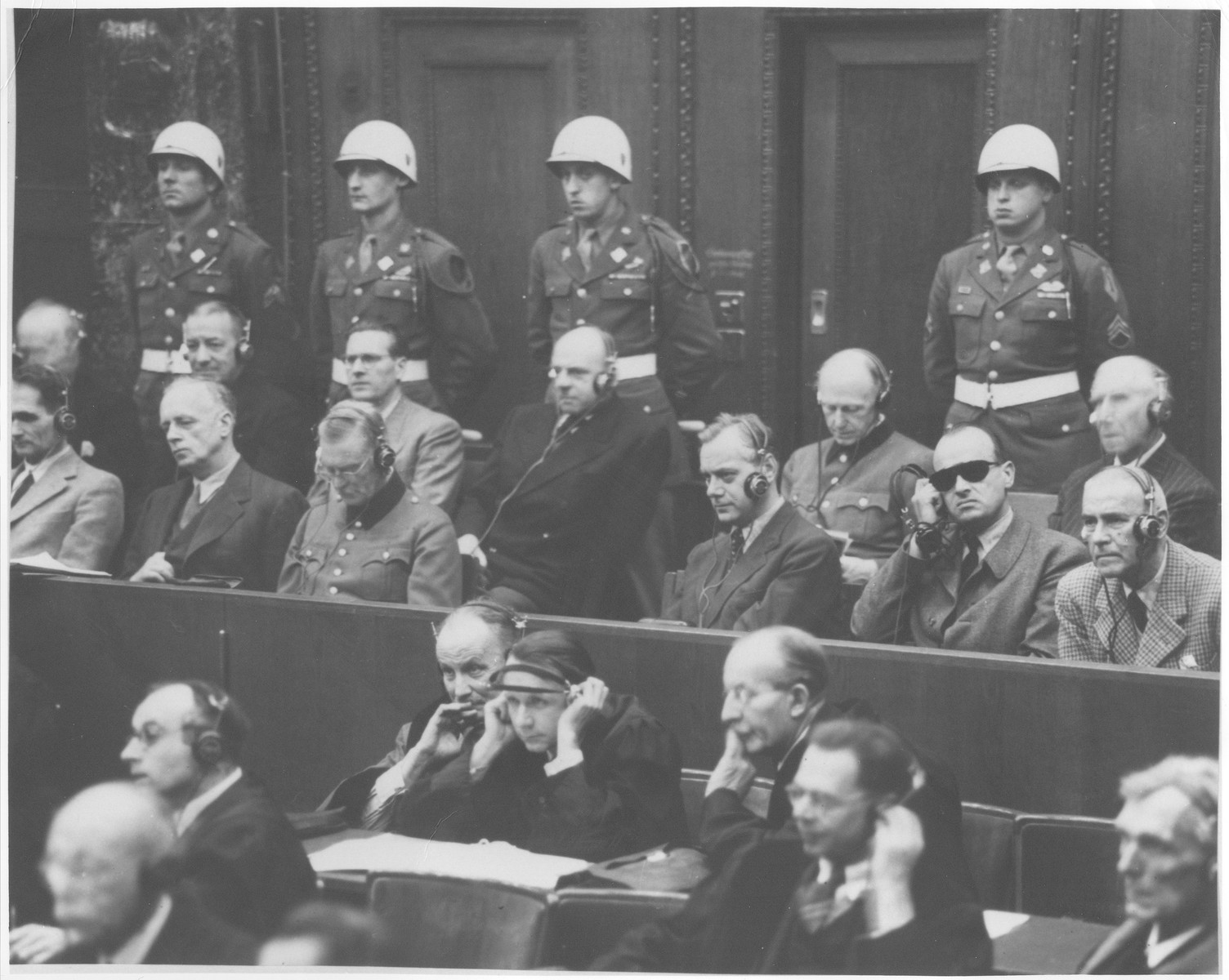 Defendants in the International Military Tribunal war crimes trial in Nuremberg sit in the prisoners' dock in front of a row of American military police.