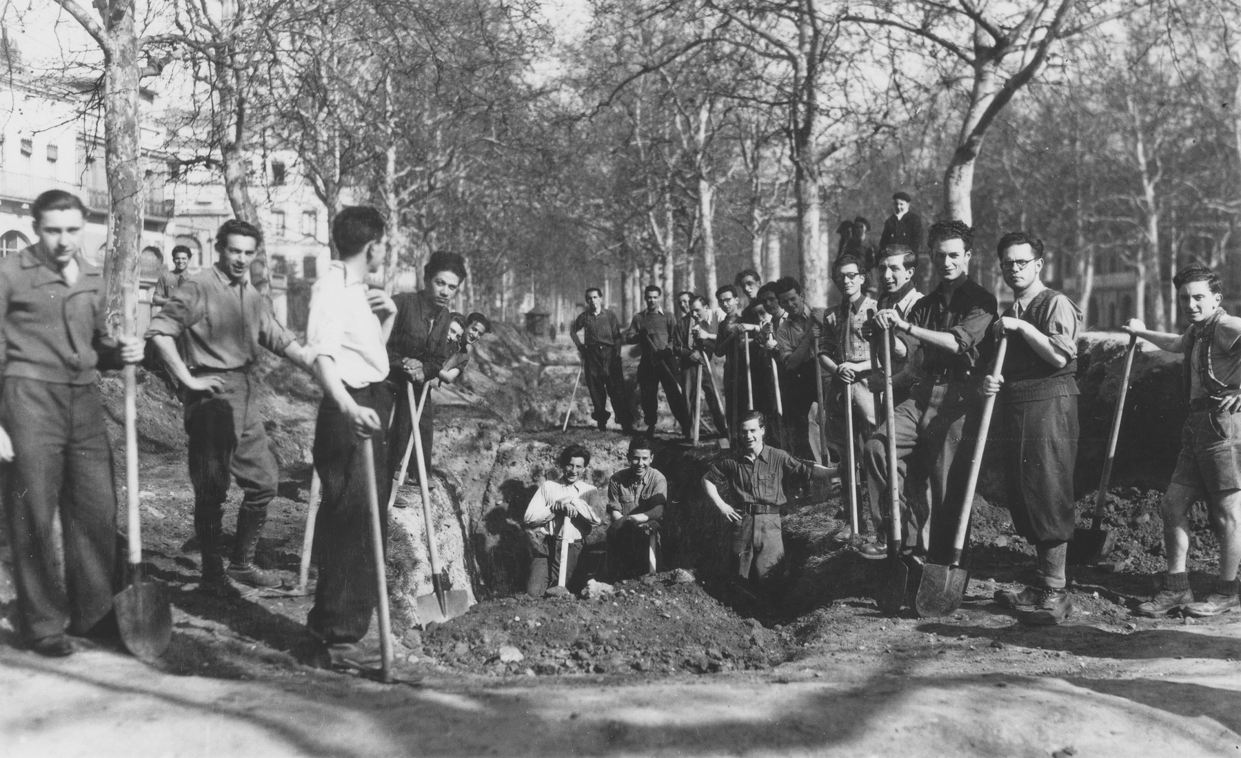 Jewish youth from the Union de la Jeunesse Juif pose with shovels alongside a trench they are filling with dirt after the liberation.