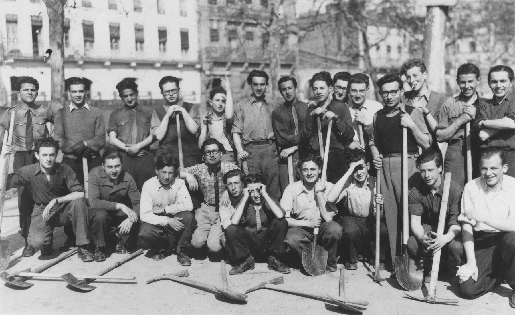 A group of Jewish boys from the Union de la Jeunesse Juif poses with shovels that they are using to fill in trenches after the war.