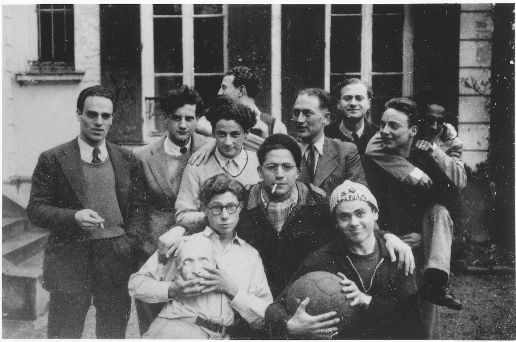 Group portrait of teenage boys at the OSE children's home, Le Vesinet.  Among those pictured is Jacques Lavelle, center, with a cigarette in his mouth.