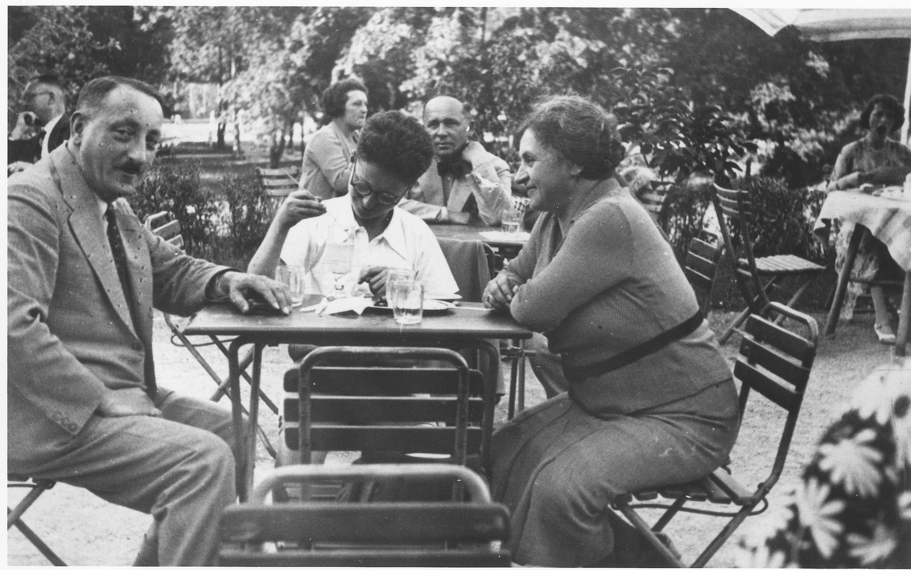Robert and Elizabeth Benda sit with their son Heinz in an outdoor cafe.