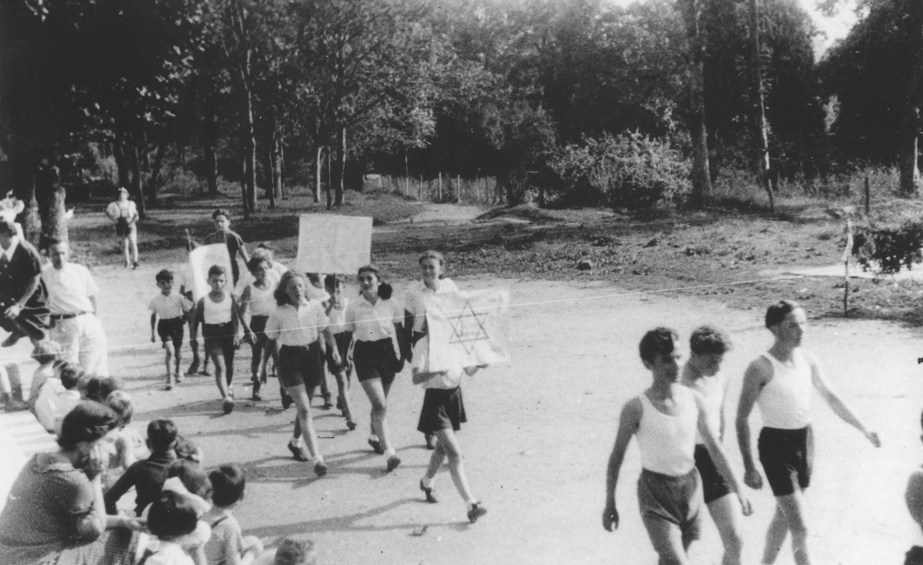Jewish refugee children march with signs in front of the Chabannes children's home on sports day.  Among those pictured are Gerard Rosenzweig, Alex Kramskoi, Angel Haas, Louise Bontnik, Elsi Wolf, Anatole Zilberstein and Stephan Lewy.