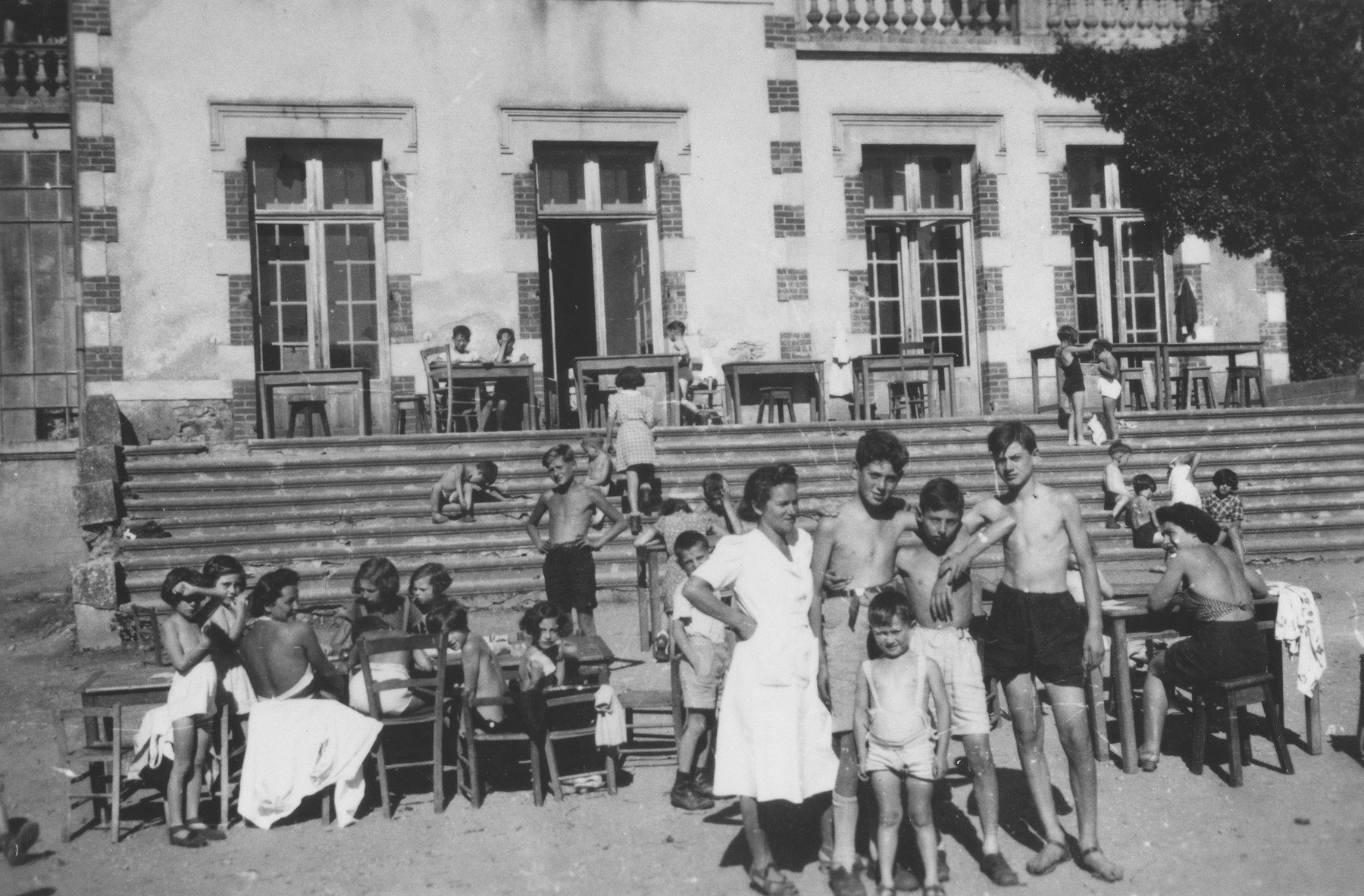 Jewish refugee children and staff members of the Chabannes children's home relax in the sun outside the home.