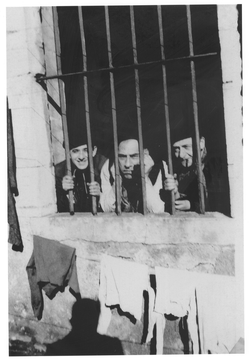 Three men look out from behind bars at the Bayonne camp in Sosua.