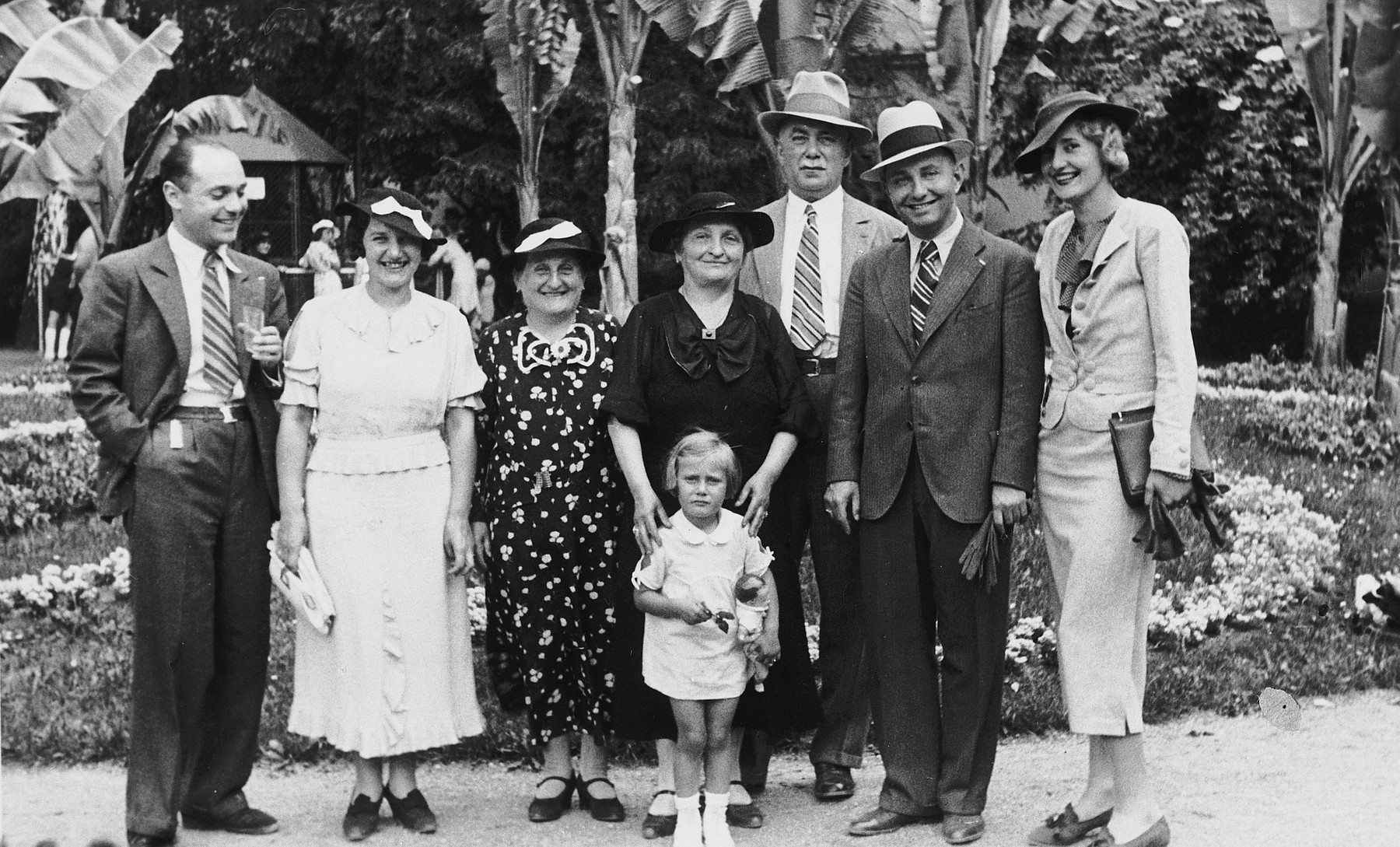The extended Margolius family poses for a family portrait in a formal garden.  From left to right are Ota and Katerina Margolius, an unknown older woman, Ota's parents Gisela and Gustav, their daughter Ines, and his brother Franticek with his wife.